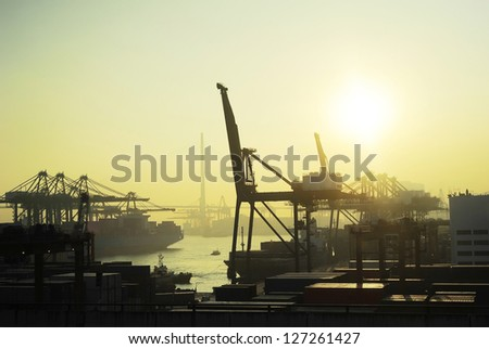 Hong Kong comercial container port at sunset - stock photo
