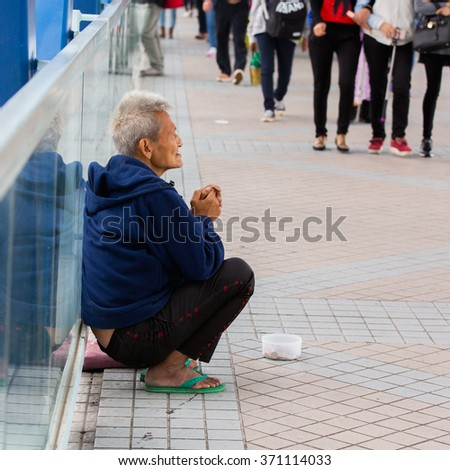 HONG KONG - DECEMBER 13, 2015 :Chinese beggars to beg for money on the overpass in front of building  Apple Store Hong Kong. - stock photo