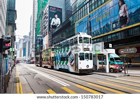 HONG KONG - FEBRUARY 21: Double trams with advertisements at Hennessy Rd. Road show provides advertisements to the passengers of public vehicles on Febuary 21,2013 in Hong Kong. - stock photo
