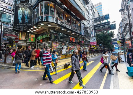 HONG KONG - JAN 18, 2015: Hong Kong cityscape view. People walking on crossroad at crowded streets with skyscrapers and shopping malls - stock photo