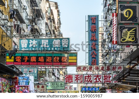 HONG KONG - MARCH 28 : Billboards in the old street on March 28, 2013 in Hong Kong. With land mass of 1104 km and 7 million people, Hong Kong is one of most densely populated areas in the world. - stock photo