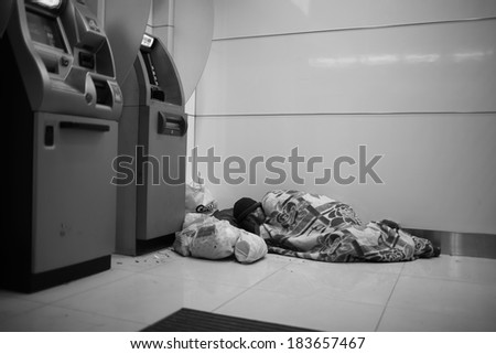 HONG KONG,MARCH 2: Homeless man live in the bank 24 hour ATM machine  in mongkokon March 2 2014.There isn't enough welfare program of HK governement to help the poor - stock photo