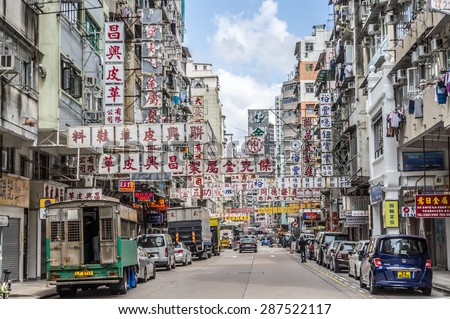 HONG KONG - MAY 8: Billboards in the old street on May 8, 2015 in Hong Kong. With land mass of 1104 km and 7 million people, Hong Kong is one of most densely populated areas in the world. - stock photo