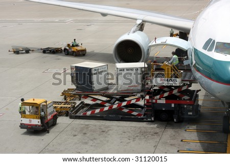 HONG KONG - MAY 16: Cargoes being unloaded from a Cathay aircraft at Hong Kong airport on May 16, 2009 in Hong Kong. Aside from China Airlines, Cathay is one of the most busy carriers in the region. - stock photo