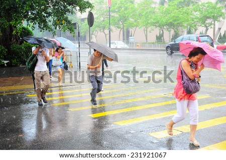 HONG KONG - MAY 20, 2013: People crossing the road in the rain.  With a land mass of 1,104 km and population of 7 million people, Hong Kong is one of the most densely populated areas in the world - stock photo