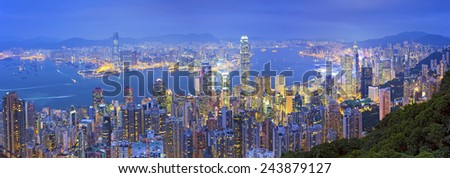 Hong Kong Panorama. Panoramic image of Hong Kong with many skyscrapers during twilight blue hour. - stock photo
