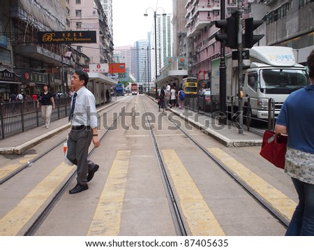 HONG KONG - SEPTEMBER 23: Unidentified people walking between city tram and wet market on September 23, 2011.Chun Yeung Street is the only place where Hong Kong trams co-exist with the wet market. - stock photo