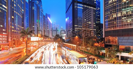 Hong Kong street with busy traffic and skyscraper office at dusk. - stock photo