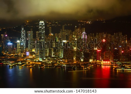 HONK KONG � JULY 14: Night view of Hong Kong cityscape from Kowloon island. Hong Kong is one of the world's leading international financial centers and has a major capitalist service economy. - stock photo