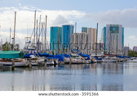 Honolulu Harbor sail boat with skyscrapers in the background - stock photo
