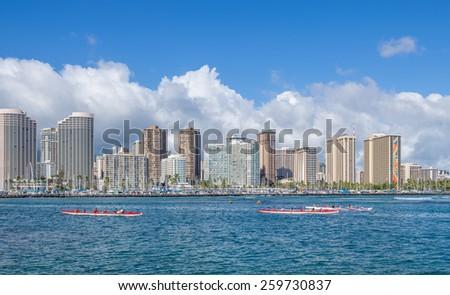 Honolulu, Hawaii, USA.  March 11, 2015:  Outrigger canoes pass by the Waikiki Resorts. - stock photo