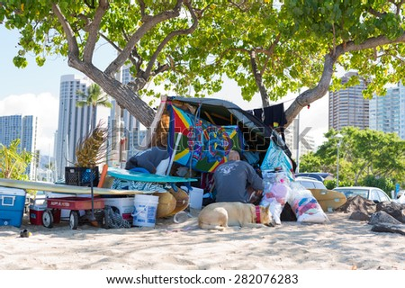 Honolulu, Hawaii, USA, May 28, 2015: Homeless man and his dog camping on a beach in Waikiki with landmark hotels in the background. The homeless problem in Hawaii affects tourists and locals. - stock photo