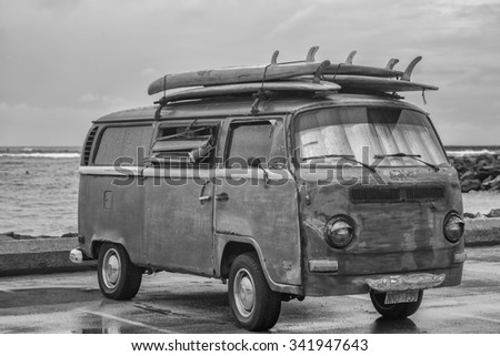 Honolulu, Hawaii, USA, Nov. 23, 2015:  Rainy morning view of an antique surfing van and old surfboards with Ala Moana Bowls surfing spot in the background.  Ancient surf vans are  popular in Hawaii. - stock photo