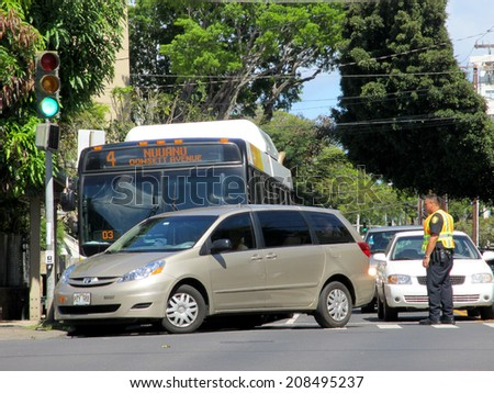 HONOLULU - MAY 6:  Honolulu City Bus has accident with Mini Van on busy street as Police Officer directs traffic Makiki, Oahu, Hawaii May 6, 2012. - stock photo