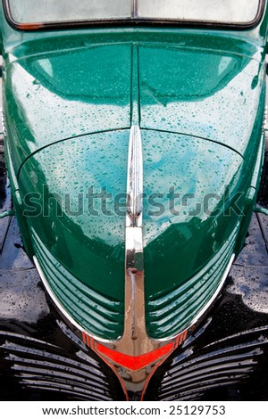 Hood of a green and black antique truck with raindrops - stock photo