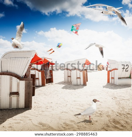 Hooded chairs on sand beach. Sea gulls and kites flying in blue cloudy sky. Vacation background. North sea coast, travel destination - stock photo
