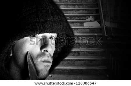 Hooded criminal with knife about to attack victim - stock photo