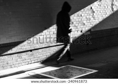 hooded figure in shadow with tiles - stock photo