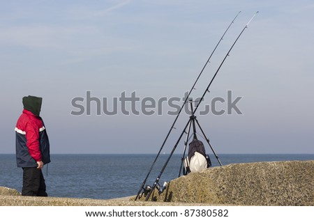 Hooded fisherman on a stone jetty watching his rods - stock photo