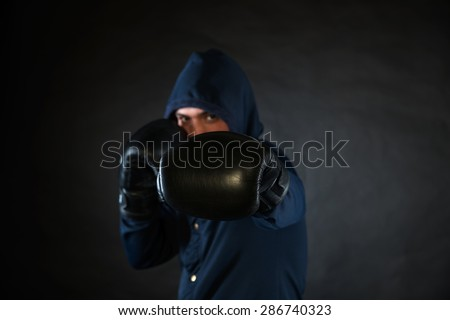 hooded man in a fighting stance with black boxer gloves
