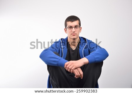 Hooded young man sitting against wall - stock photo