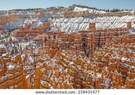Hoodoos, canyon walls, and fins make a striking contrast against the snow in Bryce Canyon National Park - stock photo