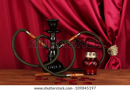 hookah on a wooden table on a background of red curtain close-up - stock photo