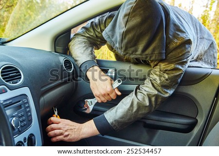 Hooligan breaking into the car - stock photo