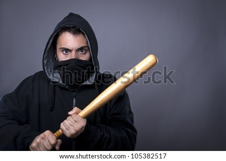 Hooligan with baseball bat ready for fight - copy space - stock photo