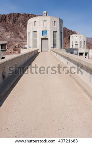 Hoover Dam's culptured turrets rising seamlessly from the dam face and clock faces on the intake towers set for the time in Nevada and Arizona. - stock photo
