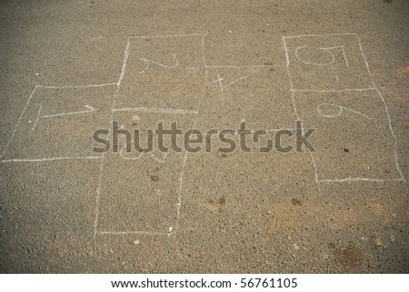 Hop scotch game drawn out on a road surface with white crayon - stock photo