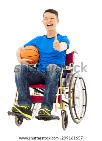 hopeful young man sitting on a wheelchair with a basketball and thumb up - stock photo