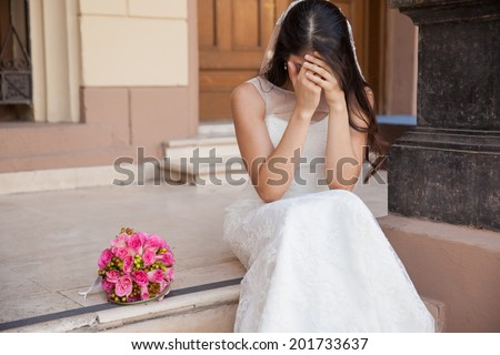 Hopeless bride crying outside a church after being stood up on her wedding day - stock photo