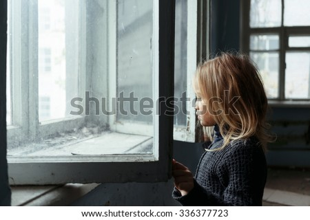 Hopeless glance. Poor unhappy cheerless girl looking outside and standing near window while feeling hopeless - stock photo