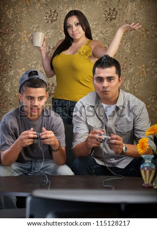 Hopeless mother behind father and son playing video games - stock photo