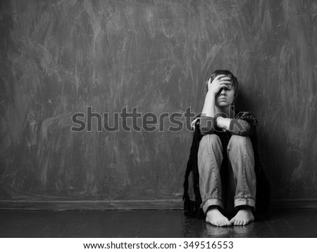 Hopeless woman is sitting against the wall. Black and white - stock photo