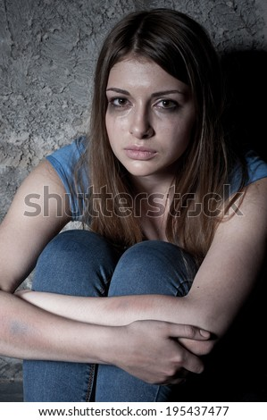 Hopeless woman. Top view of young woman crying and looking at camera while sitting against dark wall - stock photo