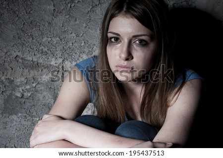 Hopelessness. Top view of young woman crying and looking at camera while sitting against dark wall - stock photo