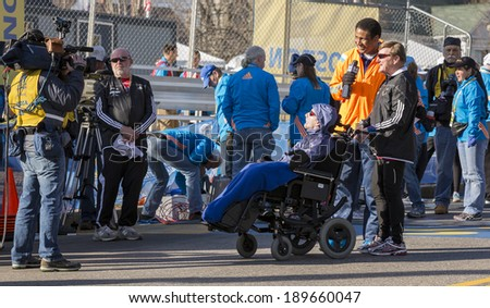 HOPKINTON, USA - APRIL 21: Athlete with disability getting interviewed by a local radio station at the starting line of the Boston Marathon 2014 in Hopkinton, Massachusetts, USA on April 21, 2014. - stock photo