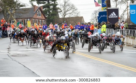 HOPKINTON, USA - APRIL 20: Athletes with disabilities competing in the Boston Marathon 2015 a few seconds after the start of the race in Hopkinton, MA, USA on April 20, 2015. - stock photo