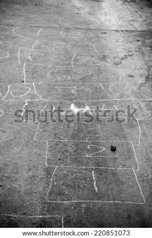 Hopscotch game drawn out on a road surface with white crayon - shallow depth of field - stock photo