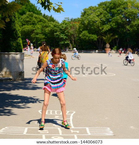 hopscotch, girl jumps in summer park outdoor - stock photo