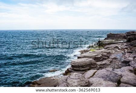 Horizon and rocky coastline with ocean waves splashing on shore under cloudy sky, in Newfoundland, Canada. - stock photo