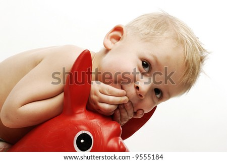 Horizontal close up of a little boy hands to his mouth looking up smiling - stock photo