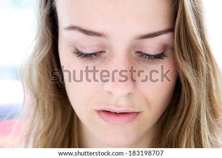 Horizontal close up portrait of a beautiful young woman looking down. Calm, peaceful expression - stock photo