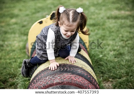 horizontal close up portrait of a little blonde girl climbing on top of painted tires in a children's playground in spring and looking happy - stock photo