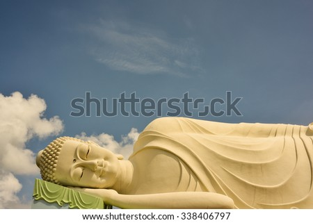 Horizontal, close up shot of a large, reclining Buddha statue surrounded by blue sky and white clouds. This was shot looking up at the statue. The statue is in Vietnam at a Buddhist Temple.  - stock photo