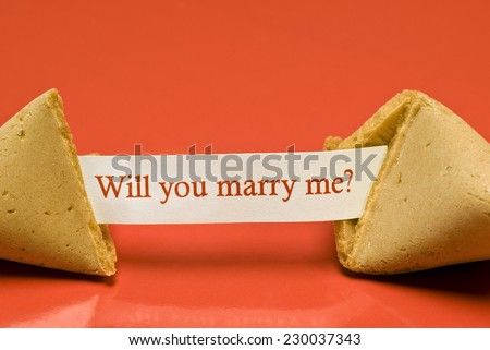 Horizontal Close Up Shot Of Broken Fortune Cookie With Paper Saying, Will You Marry Me? - stock photo