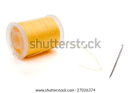 Horizontal closeup of a yellow spool of thread and a needle - stock photo