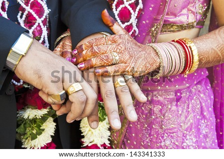 Horizontal color capture taken at a hindu wedding in Surat India. Photo session after the ceremony of the happy hand holding couple displaying their rings of matrimony and the bride lays her claim - stock photo
